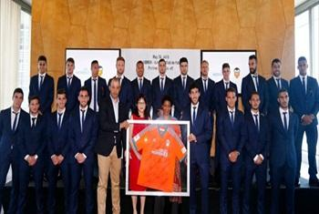 UN Women Executive Director Phumzile Mlambo-Ngcuka holds one of the new jerseys as she poses with players of the Valencia Club de Futbol soccer team at a press conference in New York on 26 May 2015.