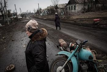 Residents walk along the main road of Nikishino village in eastern Ikraine.