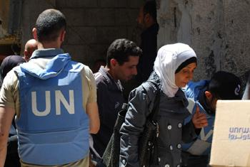 An UNRWA staff member assists Syrians with food aid in Yarmouk, Damascus.