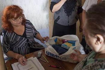 A woman collects aid items at a distribution centre in Nikolayevka, eastern Ukraine. UNHCR File Photo/E. Zivatdinov