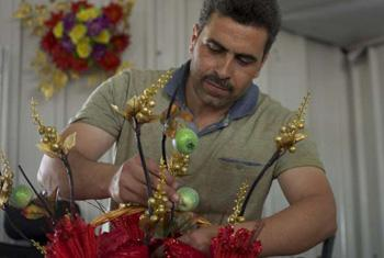 Mohammad, 42, from Syria's southern Dara'a governorate arranges artificial flowers in colourful displays in his temporary shop in Jordan's Azraq refugee camp. © UNHCR/C.Dunmore