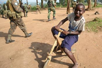 Aveba, Ituri district, DR Congo: A young girl riding her toy wooden bicycle flashes a confident smile as a patrol of MONUSCO peacekeepers passes by. Photo MONUSCO/Abel Kavanagh