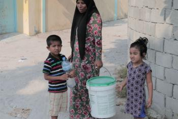 A woman from the Island of Gaafu Dhaalu Atoll Thinadhoo Island on her way to collect water with her two grandchildren.