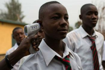 A boy's temperature is taken as he arrives at school in Kenema, Sierra Leone (March 2015). File
