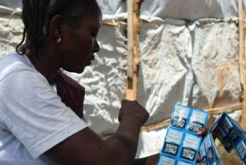 A health worker in South Sudan counts water purification sachets for distribution to patients upon being discharged from the cholera treatment unit.