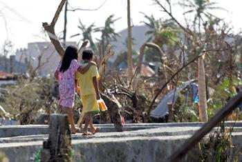 Two children walk past downed trees and other destruction caused by Super Typhoon Haiyan in Tacloban City.