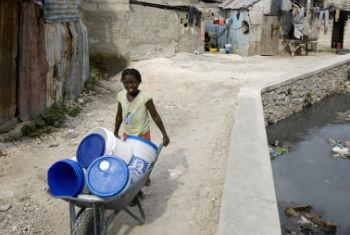 A girl carries empty buckets to get clean water at a water distribution point in Port au Prince, Haiti.