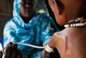 A nurse measures the arm of a severely malnourished child at a clinic in Sudan. UN File Photo/Albert González Farran.