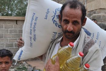 A farmer collects food ration for his family. An estimated 12 million Yemenis are food insecure.