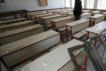 On 28 April, the son of the guard at Ibn Sina School walks through rows of desks while checking a damaged classroom in the facility, in Sana'a, the capital.