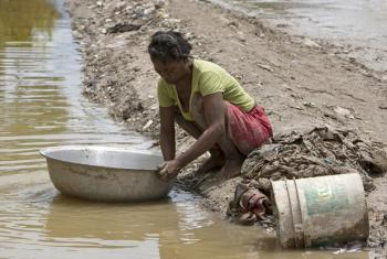 "A woman washes her mud soaked clothes and sheets along the side of the road in the aftermath of the tropical storm ""Hanna"" that left the entire region flooded and thousands of people stranded. UN File Photo/Logan Abassi"
