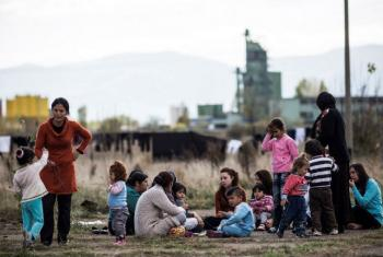 Migrants and asylum-seekers, mostly Syrian Kurds, sit in the yard outside a schoolhouse-turned-reception centre, on the outskirts of the Bulgarian capital Sofia.