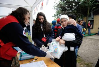 A woman carrying a young child receives relief items for her family, at a Red Cross station set up outdoors at the reception centre for refugees and migrants, in the town of Šid, Serbia, on the border with Croatia.