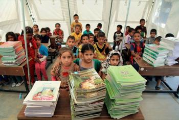 Students sit in front of new textbooks in one of 12 tented classrooms at Al Takiya Al Kasnazaniya camp for internally displaced persons in Karkh District, Baghdad Governorate, Iraq.