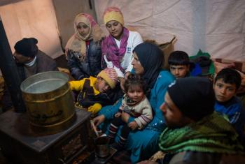 Members of a Syrian refugee family huddle around a stove inside their shelter in Lebanon's Bekaa Valley. File