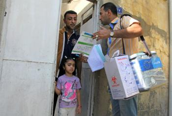 A health worker gives a cholera prevention and treatment pamphlet to a family in Sadr City, Baghdad.