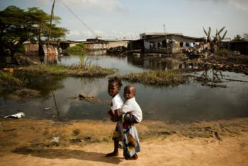 A girl carries her toddler sibling as she walks beside along a pool of floodwater in the city of Cotonou, Benin. File