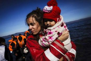 A volunteer on the Greek Island of Lesvos gathers a baby girl in her arms, moments after her family arrived in an inflatable boat.