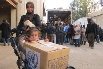 A mother and child receive UNRWA food assistance at the distribution areas in Yalda, on the southern outskirts of Damascus to the west of the Yarmouk Camp.