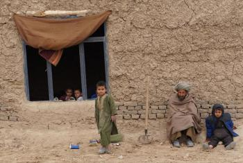 Members of a family sit outside their simple home in northern Afghanistan's Faryab province.