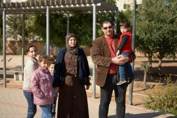 Syrian chef Mahmoud and his wife Rasha pose with their four young children at a local park in the Jordanian capital Amman.