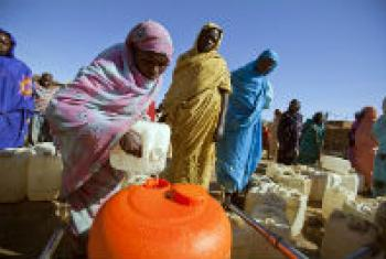 Women filling an orange Water Roller at a water distribution point in Sudan.