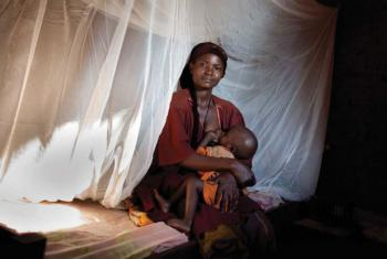 Woman and her child protected by insecticide-treated bed net. File