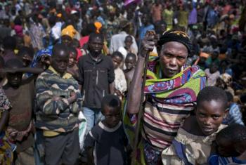 An elderly woman waits among a crowd of other Burundian refugees for assistance in Rwanda's Mahama Refugee Camp. File