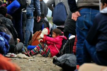 A girl sits on the ground and plays with her toy bear, as people queue around her at the Vinojug reception centre near the town of Gevgelija, in the former Yugoslav Republic of Macedonia.