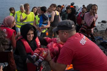 Volunteers help newly-arrived refugees on the shores near the town of Mithymna, on the Greek island of Lesbos, in the North Aegean region.