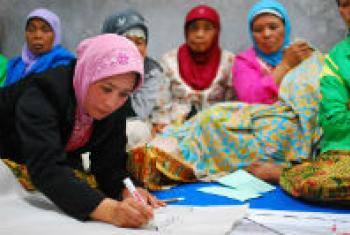 Women at a community meeting discuss the reconstruction of their village in Indonesia.