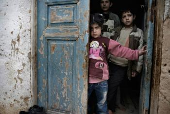 Syrian children shelter in a doorway amid gunfire and shelling.