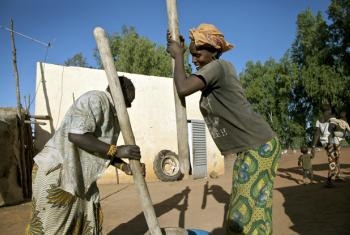 Two women grind rice outside a water pump station in the area of Koroyomme, Timbuktu.