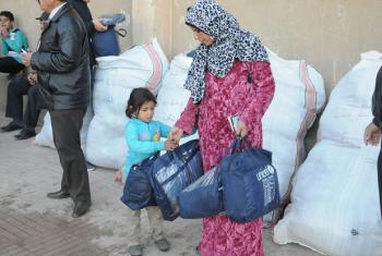 Displaced Syrians receive UNICEF winter clothing kits.