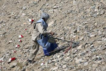 De-mining expert detects anti-personnel land mine for clearance.