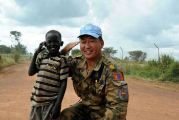 A Mongolian troop with the UN's mission in South Sudan (UNMISS) smiles for the camera with a local boy in Bentiu, Unity State. UN File Photo/Isaac Billy