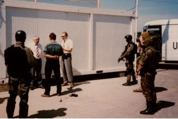 Slavko Dokmanovic (left, in white shirt) is read his rights by Vladimir Dzuro (right, in white shirt). File Photo (1997): Col. David Jones, US Army