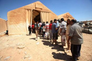Syrian refugees queue for relief items at Jordan's Za'atri camp.