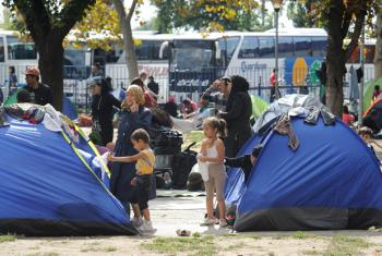 Children, women and men who have fled their homes amid the ongoing refugee and migrant crisis, stand outside small tents in a park next to the bus and train stations in Belgrade, the Serbian capital.