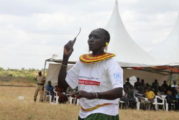 A woman holds a knife used in Female Genital Mutilation/Cutting (FGM/C).