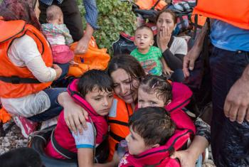 A Syrian mother cries with relief as she embraces her three young children after a rough sea crossing. File