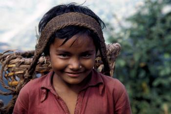 In Nepal, a young girl transports agricultural goods along a 65 km. mountain path. When children engage in work that is not appropriate for their age, this is child labour.