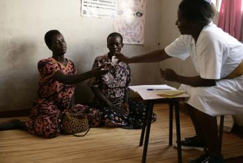 Two HIV-positive women in Uganda sit on the floor while a Registered Nurse (RN) gives them anti retroviral drugs (ARVs).
