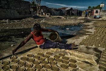 """A woman working for a collective prepares """"clay cakes,"""" sun-baked disks of clay, butter and salt, which have become a symbol of Haiti's struggles with extreme poverty and hunger."""