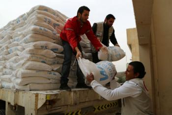 Syrian Arab Red Crescent volunteers distribute bags of WFP wheat flour to internally displaced families in Syria (2015). File
