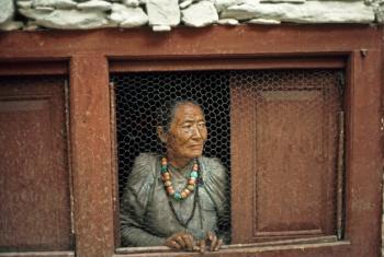 An elderly woman at her window in a Nepalese village.