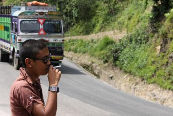 A man smokes on the side of the road as a bus passes in Nepal.