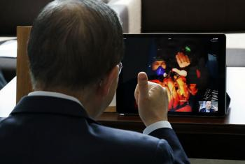 """Secretary-General Ban Ki-moon (left) gives Captain Bertrand Piccard (on screen) a """"thumbs up"""" during their video chat via Skype. Captain Piccard and André Borschberg have flown their expirmental aircraft, Solar Impulse 2, around the world powered only by"""
