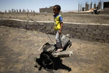 Boy playing on piece of exploded artillery shell which landed near his home, in the village of Al Mahjar, a suburb of Sana'a (April 2015). File
