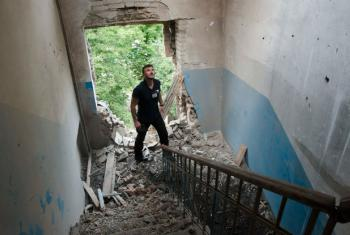 A monitor from the Organization for Security and Co-operation in Europe (OSCE) Special Monitoring Mission to Ukraine inspects damage to a building. File